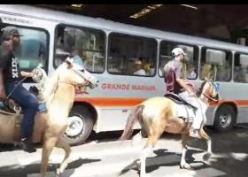 Homens montados em cavalos na área restrita a ônibus no terminal de...