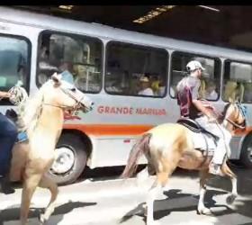 Homens montados em cavalos na área restrita a ônibus no...
