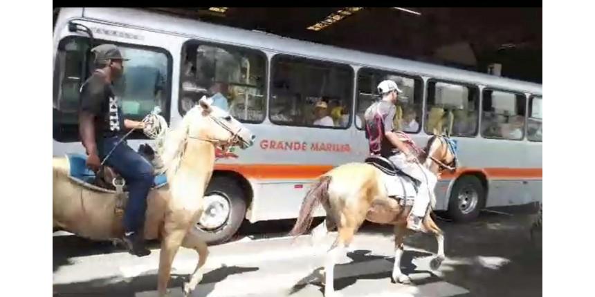 Homens montados em cavalos na área restrita a ônibus no terminal de Marília