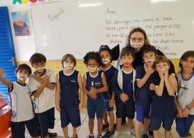 Crianças usam fitas no rosto para que colega com...