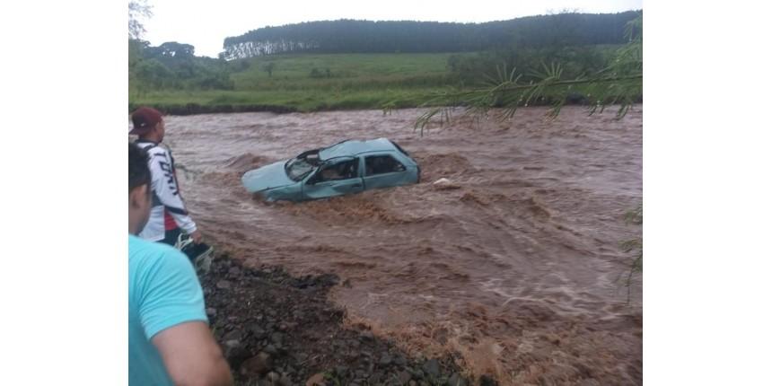 Carro é arrastado por enxurrada e cai em rio durante chuva