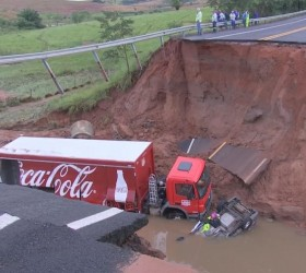 Chuva abre cratera na pista e 'engole' carro e caminhão...